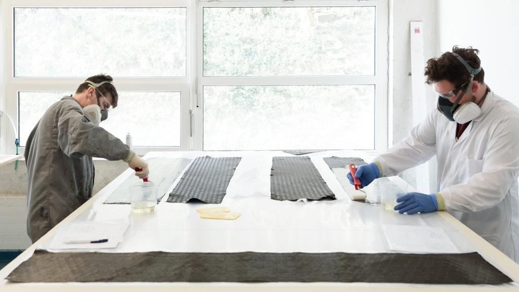 Fabrice und Florian imprägnieren Carbonschichten vor dem Auftragen mit Harz
