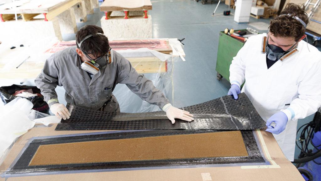 Fabrice Allaz und Florian Bernhard bringen die letzten Kohlefaserschichten auf die Haut der Flosse auf, um die Wabenstruktur zu unterteilen